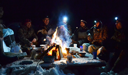 les retrouvailles autour du feu de camp durant un raid chien de traîneau en Laponie suédoise