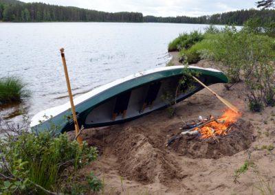 canoë déposé sur la rive de la rivière Örån et feu de camp pour le bivouac du soir