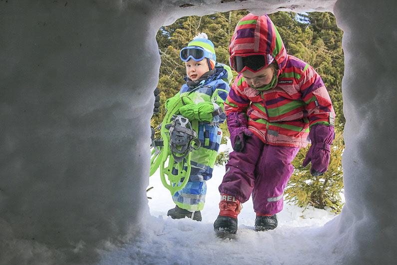 enfants en tenue de neige en activité chiens de traîneau en laponie suédoise rentrent dans un igloo